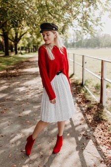 Atemberaubende blondine mit trendigem roten pullover und stilvollem kleid mit dunklem, schönem hut. schönes modell, das souverän unter abgefallenen blättern aufwirft.