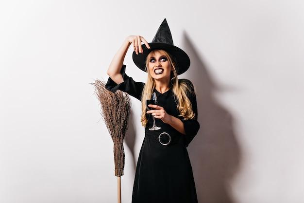 Atemberaubende böse hexe mit besen. spektakuläre frau mit dunklem halloween-make-up, das lustige gesichter macht.