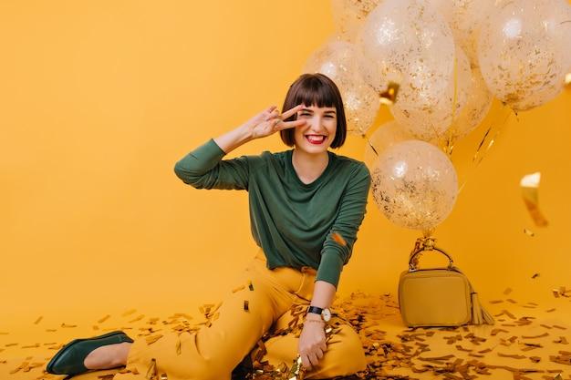 Atemberaubende braunhaarige dame, die mit friedenszeichen nahe partyballons aufwirft. innenaufnahme des lachenden fröhlichen mädchens, das geburtstag feiert.