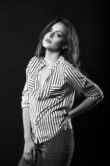 Atemberaubende brünette frau mit langen lockigen haaren trägt gestreiftes hemd, das im studio posiert. schwarz-weiß-porträt