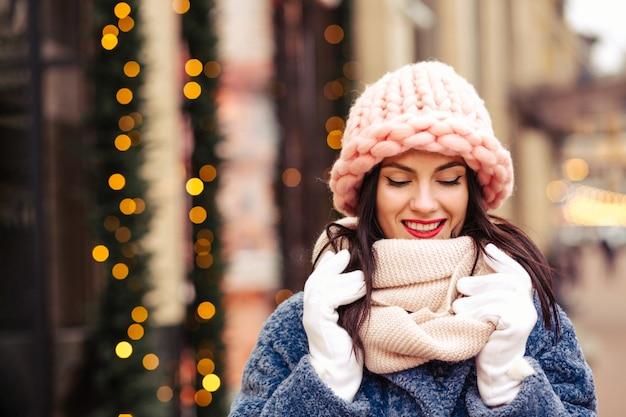 Atemberaubende brünette frau trägt gestrickte hellrosa mütze und schal, die durch die mit girlanden geschmückte stadt spaziert. platz für text
