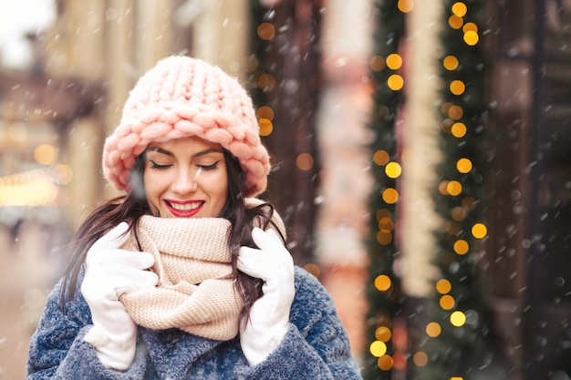 Atemberaubende brünette frau trägt gestrickte hellrosa mütze und schal, die während des schneefalls in der stadt spazieren gehen. platz für text