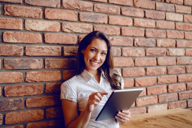 Atemberaubende brünette im hemd, die im café sitzt, sich auf backsteinmauer stützt und tablette beim betrachten der kamera verwendet.