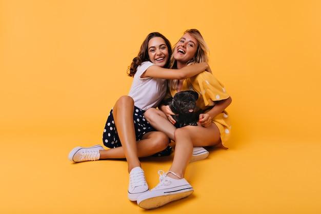 Atemberaubende brünette mädchen in weißen schuhen, die ihre schwester mit glücklichem lächeln umarmen. sorglose blonde dame, die spaß mit bester freundin und bulldogge während des porträtschießens auf gelb hat.