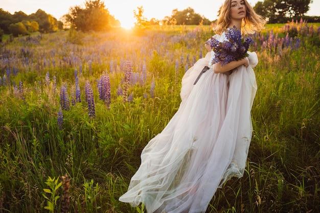 Atemberaubende dame im weißen kleid steht mit blumenstrauß auf dem feld