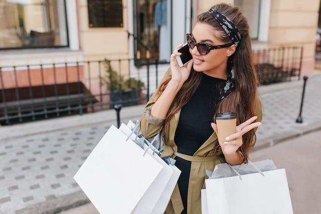 Atemberaubende dunkelhaarige modische frau, die an einem sonnigen tag am telefon spricht und große pakete von der boutique trägt