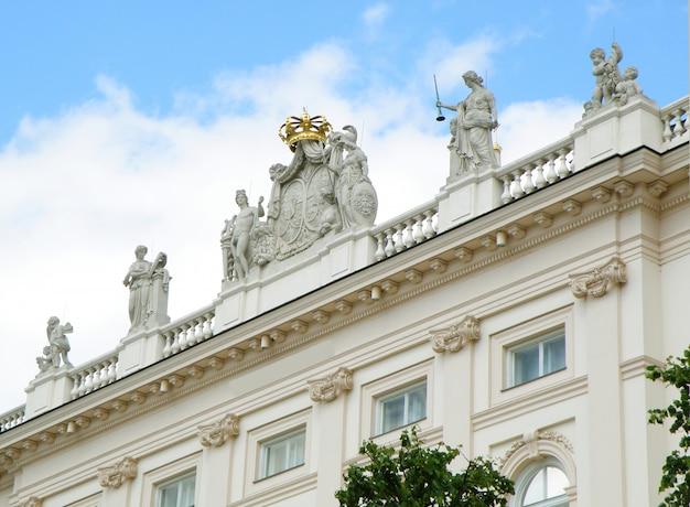 Atemberaubende fassade mit vielen schönen skulpturen eines weißen gebäudes in wien, österreich