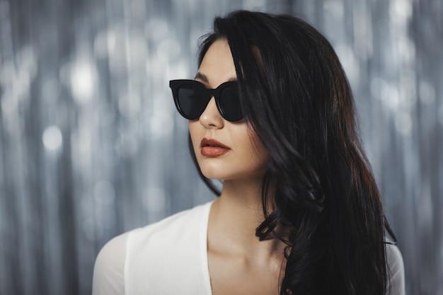 Atemberaubende feiernde frau im weißen stilvollen kleid und in der sonnenbrille
