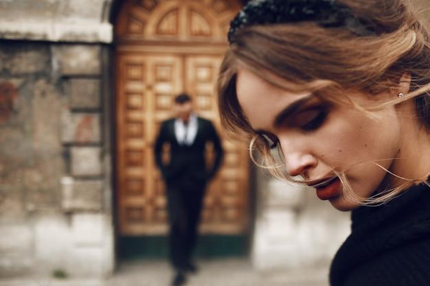 Atemberaubende frau im schwarzen mantel posiert vor einem alten gebäude