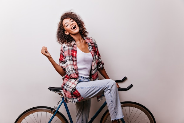 Atemberaubende frau in den blauen jeans und im roten hemd, die auf fahrrad aufwerfen. innenaufnahme des lachenden verträumten mädchens, das spaß hat.