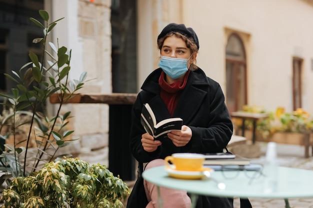 Atemberaubende frau in der medizinischen schutzmaske, die freizeit auf freiluftterrasse verbringt und neues buch liest.