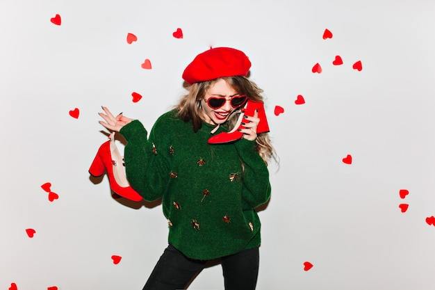 Atemberaubende frau in der roten baskenmütze, die in der selbstbewussten haltung steht und ihre schuhe hält