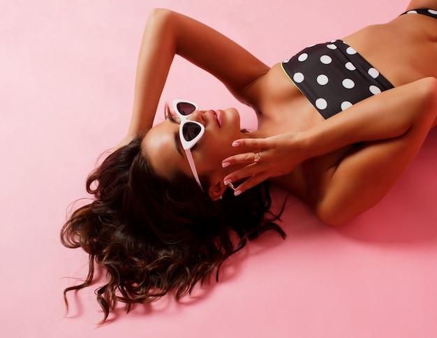 Atemberaubende frau in stilvoller badebekleidung, die auf rosa oberfläche liegt