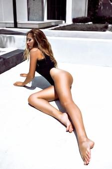 Atemberaubende frau mit schmaler passform und erstaunlichen langen beinen, die auf dem boden der villa posieren, sexy modestil. entwöhnt schwarzen körper, helle kunst schminken.