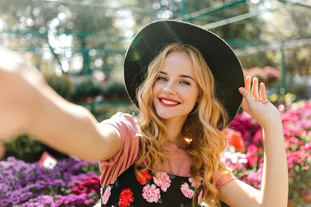 Atemberaubende frau mit schönen augen, die selfie auf orangerie machen. erfreute frau im schwarzen hut, der mit blumen aufwirft.