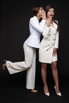 Atemberaubende freunde in weißen anzügen klatschen auf schwarzem hintergrund