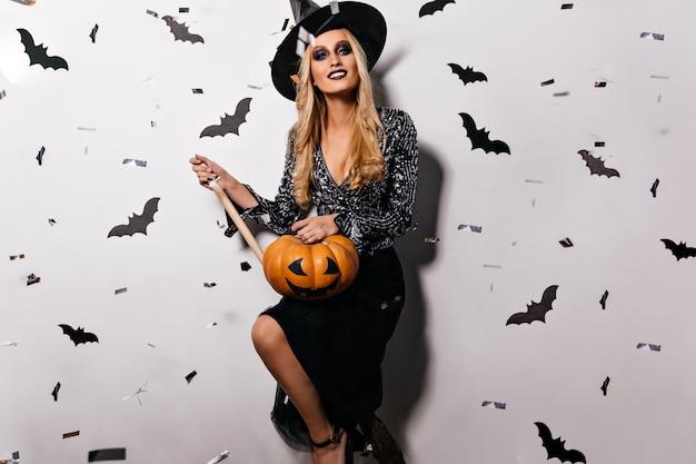 Atemberaubende hexe mit hellem make-up, das halloween-kürbis hält. glamouröse blonde frau in gruseliger kleidung, die sich auf horrorparty vorbereitet.