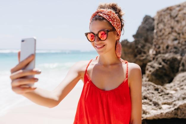 Atemberaubende junge dame in roter kleidung mit telefon für selfie am wilden strand. entzückendes weißes mädchen in der funkelnden sonnenbrille, die foto von sich macht, während sie am ozean ruht.