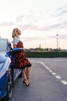 Atemberaubende junge frau, die kleid trägt, das vor ihrem auto auf der straße mit himmel im hintergrund, besitzfahrer aufwirft