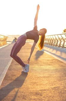 Atemberaubende junge frau im teenager-sport, die dehnübungen an der brücke macht