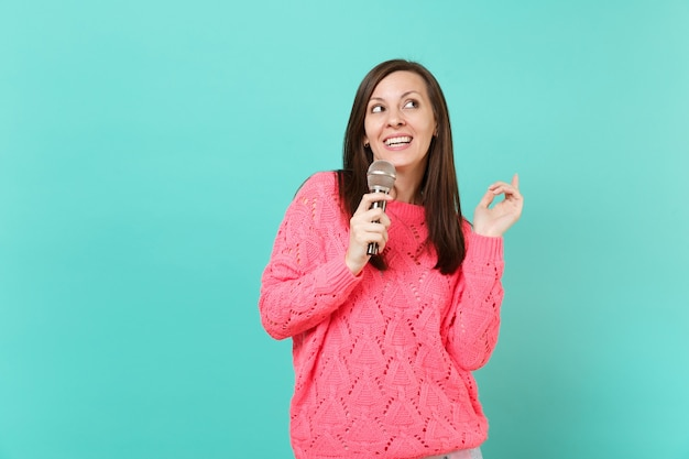 Atemberaubende junge frau in gestricktem rosa pullover, die in der hand nach oben schaut, ein lied im mikrofon singt, das auf blautürkisem wandhintergrund isoliert ist, studioporträt. menschen lifestyle-konzept. kopieren sie platz.