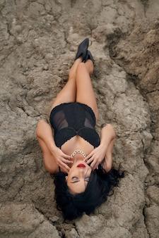 Atemberaubende junge frau mit dunklem, gewelltem haar und hellem make-up, die auf trockenem sand in der wüste liegt