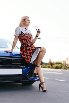 Atemberaubende junge frau waring kleid posiert vor ihrem auto im freien, eigentümer fahrer