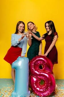 Atemberaubende junge frauen, die mit champagner, ballon in form von achtzehn anstoßen rösten
