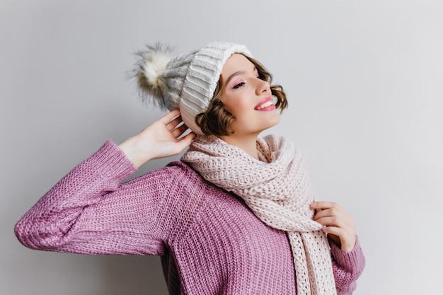 Atemberaubende kaukasische frau im lila pullover, der spielerisch aufwirft. innenfoto des anmutigen mädchens trägt weiße wollmütze und schal, die mit lächeln wegschauen.