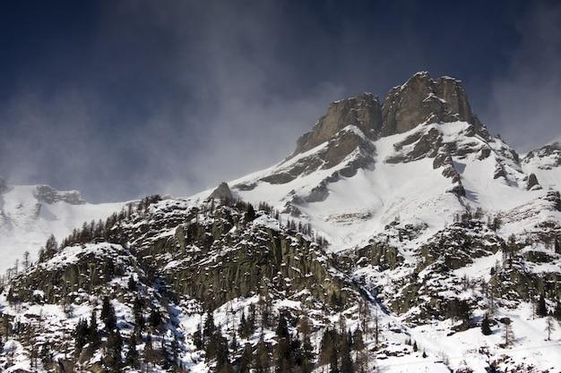 Atemberaubende landschaft der schneebedeckten berge unter einem malerischen bewölkten himmel