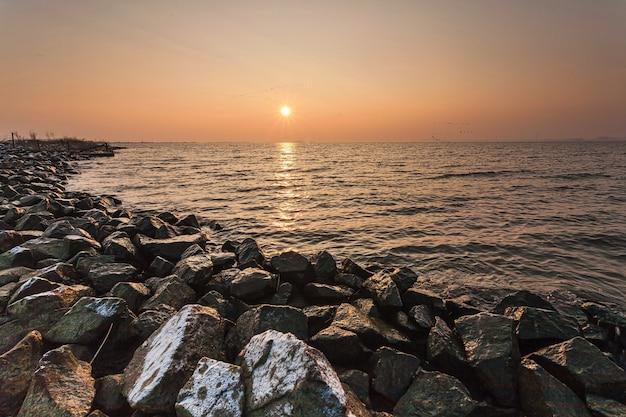 Atemberaubende landschaft des sonnenuntergangs, der im meer in den niederlanden reflektiert