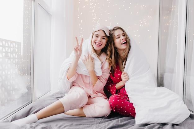 Atemberaubende lockige frau in schlafmaske, die glück ausdrückt, während sie im schlafzimmer aufwirft. zwei europäische mädchen im pyjama sitzen unter der decke.