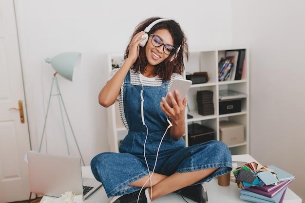 Atemberaubende schwarze dame in turnschuhen, die mit gekreuzten beinen auf dem tisch sitzen und den telefonbildschirm mit einem lächeln betrachten