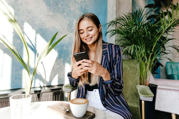 Atemberaubende sms-nachricht der weißen frau beim trinken von cappuccino. liebenswertes europäisches mädchen in der jacke, die im café ruht.