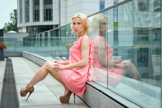 Atemberaubende sommermode atemberaubendes porträt der hübschen jungen blonden sexy frau gekleidet im kurzen rosa kleid, das in der straße aufwirft.