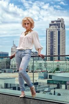 Atemberaubende sommermode atemberaubendes porträt der hübschen jungen blonden sexy frau, gekleidet in ein weißes hemd und zerrissene jeans, die in der straße aufwerfen.