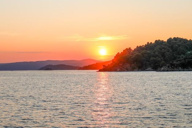 Atemberaubende sonnenuntergangslandschaft über dem meer an der skiathos-insel in griechenland