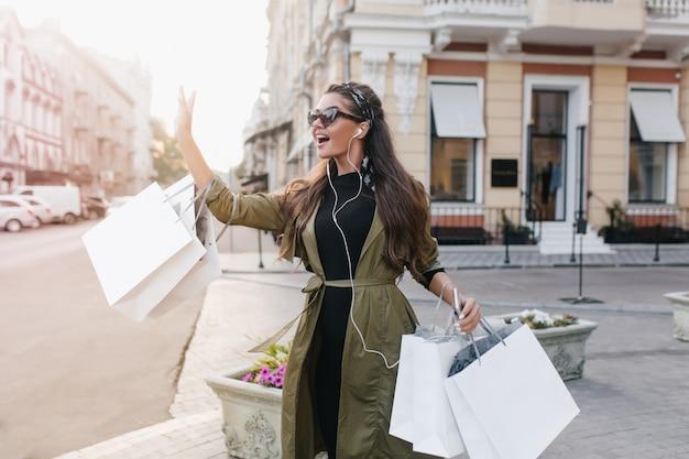 Atemberaubende spanische dame in weißen kopfhörern winkt jemandem, der mit paketen auf der straße steht, mit der hand