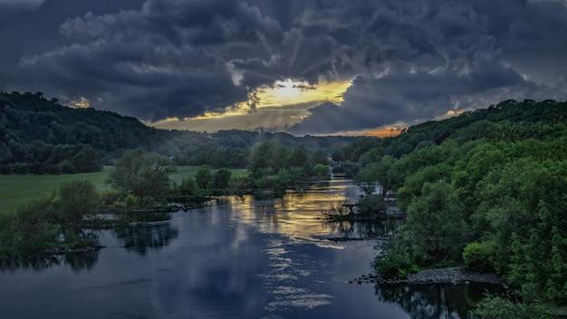Atemberaubende susnet an einem fluss mitten in einem grünen wald unter dem dunklen himmel