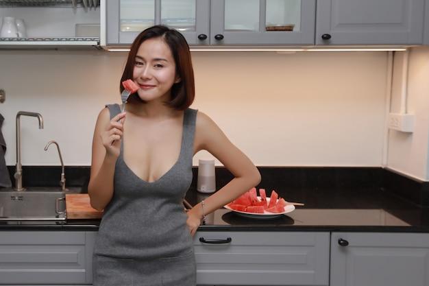 Atemberaubende und junge asiatische frau im grauen kleid, die wassermelone in der küche schneidet und schält, mit lächelndem gesicht, während sie musik von handy und mobilem lautsprecher hört
