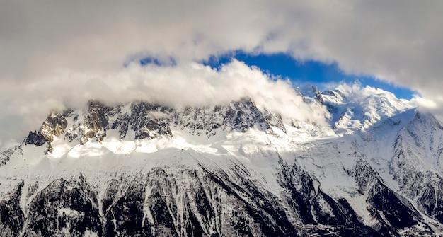 Atemberaubende vogelperspektive von mont blanc-bergspitze bedeckt mit glänzendem schnee, eis und gletschern unter blauem himmel.