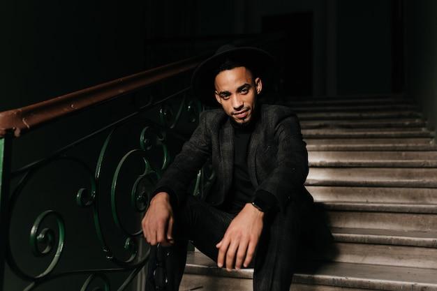 Atemberaubender afrikanischer mann, der mit sanftem lächeln auf treppen aufwirft. hübscher kerl in karierter jacke, der am abend auf stufen sitzt.