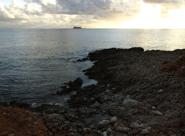 Atemberaubender sonnenuntergang über dem ozean mit der insel filfla in malta an einem wolkigen tag