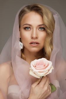 Atemberaubendes blondes modell in rosa schleier natürlichem make-up, das rosa schleier trägt und eine zerbrechliche rosa rose hält