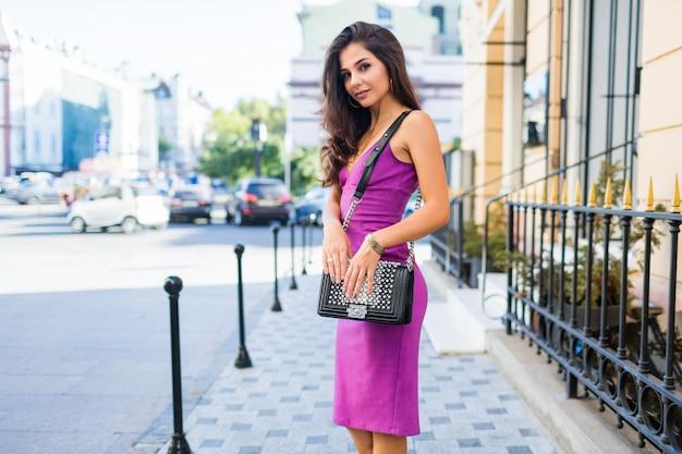 Atemberaubendes brünettes mädchen, das auf sonniger straße geht, sonniges wetter genießt, einkauft, freunde wartet, um am wochenende tolle zeit zu haben. wellenförmige frisur. lila samt sexy kleid. romantische stimmung.