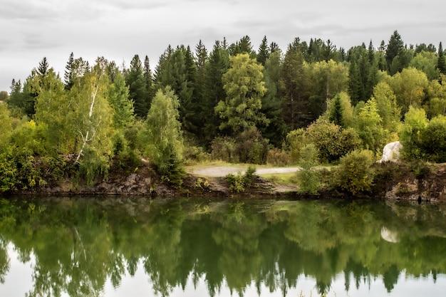 Atemberaubendes foto von herbstlaub, das auf einem see mit einer glasähnlichen spiegelwasseroberfläche reflektiert wird.