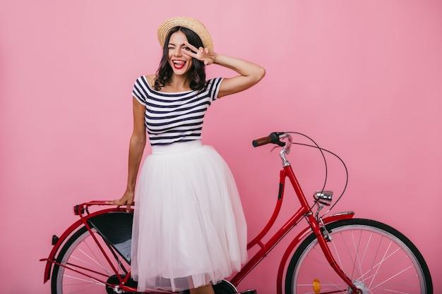 Atemberaubendes lateinamerikanisches mädchen im üppigen rock, der nahe rotem fahrrad steht. entzückende frau in den trendigen kleidern, die mit vergnügen aufwerfen.