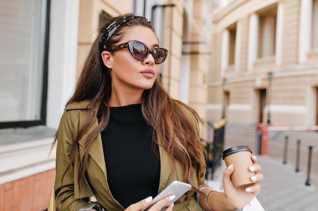 Atemberaubendes lateinamerikanisches weibliches modell mit nacktem make-up, das tasse kaffee hält und die straße entlang geht