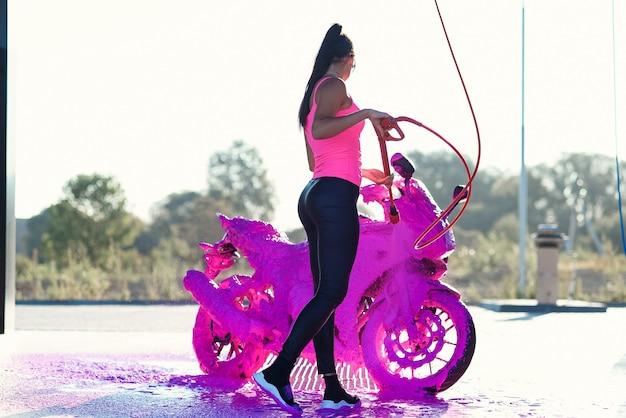 Atemberaubendes mädchen wäscht motorrad im autowaschservice mit hochdruckwasser