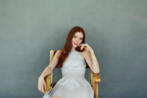 Atemberaubendes modisches junges europäisches weibliches modell mit langen ingwerhaaren, gekleidet in cocktailkleid sitzend auf holzstuhl gegen leere wand mit kopienraum für ihren inhalt